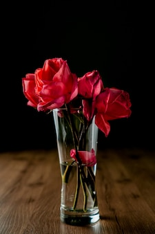 A group of pink roses puts in clear glass vase on dark color wooden table