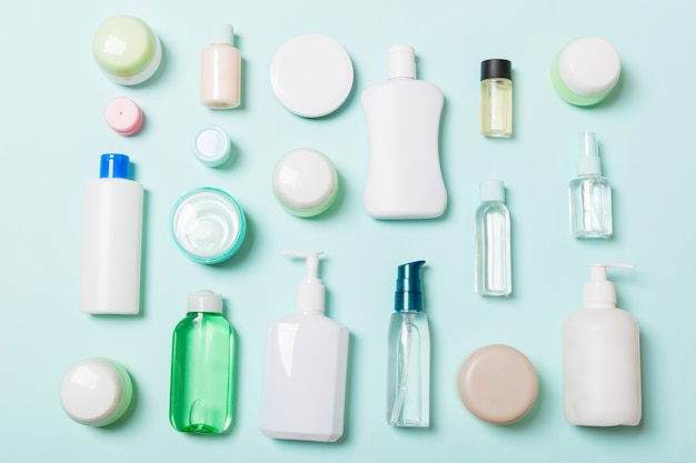 Group of plastic bodycare bottle flat lay composition with cosmetic products on blue