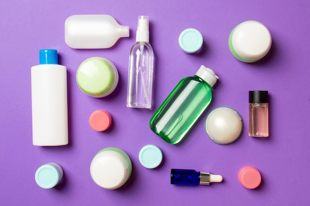 Group of plastic bodycare bottle flat lay composition with cosmetic products on colored background empty space for you design. set of white cosmetic containers, top view with copy space.