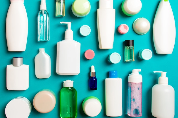Group of plastic bodycare bottle flat lay composition with cosmetic products on colored surface empty space for you design