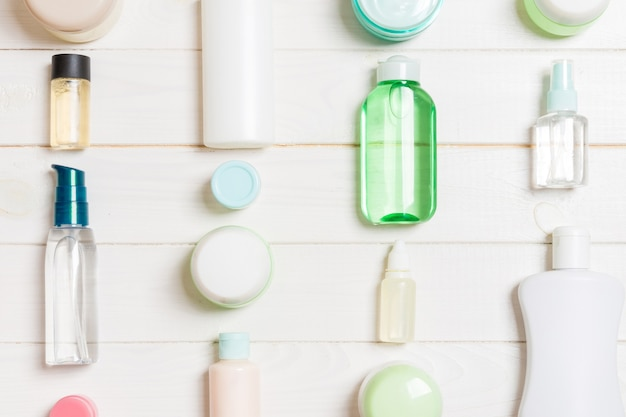 Group of plastic bodycare bottle flat lay composition with cosmetic products on wooden background empty space for you design. set of white cosmetic containers, top view with copy space.