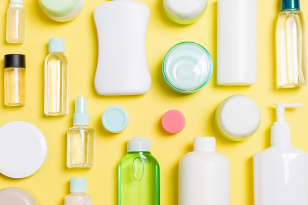 Group of plastic bodycare bottle flat lay composition with cosmetic products on yellow background empty space for you design. set of white cosmetic containers