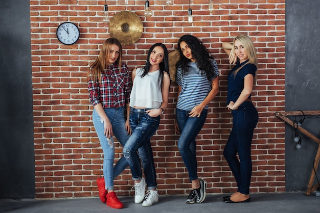 Group portrait of best friends girls with colorful fashionable clothes holding friend posing on a brick wall, urban style people having fun, s about youth togetherness lifestyle