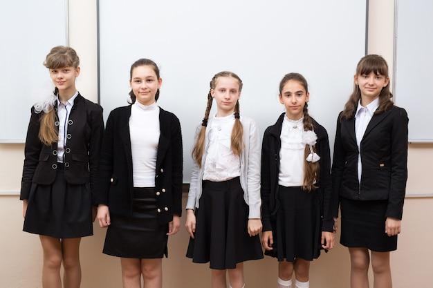 Group portrait of happy schoolchildren near the blackboard