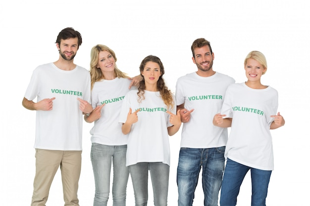 Group portrait of happy volunteers pointing to themselves over white background