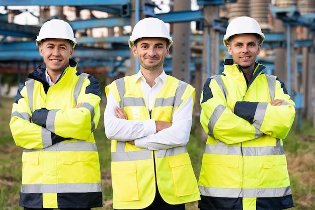 多民族の産業労働者チームのグループの肖像画は、技術者、エンジニア、メカニックウェアで構成されています