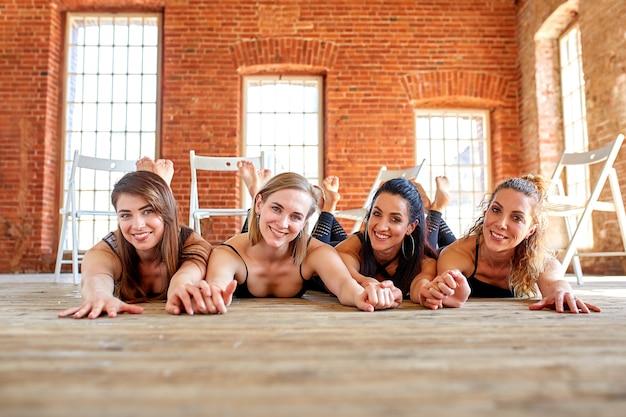若いスポーティなグループの肖像画は、笑って一緒に話している白い壁の横に立っているエクササイズマットで美しい女の子を興奮させた