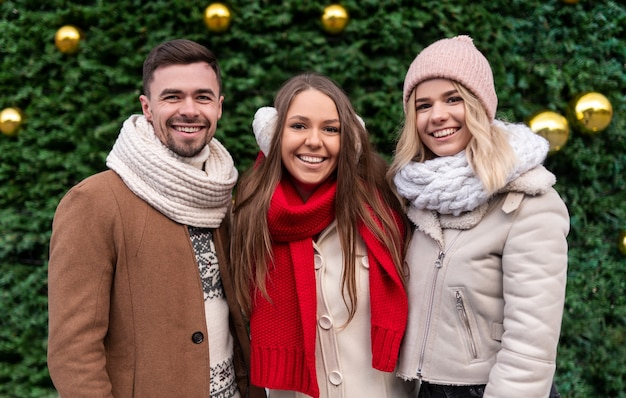 Group of positive millennial man and women in warm winter outfits smiling and looking while standing together, against green christmas tree decorated with golden balls