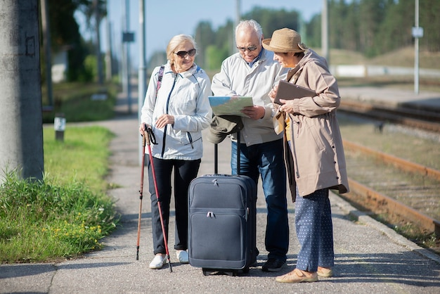 Group of positive senior people looking at map on traveling journey.