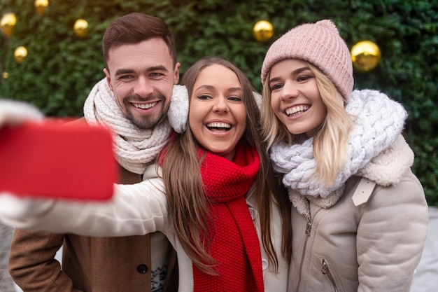 Group of positive young friends in warm winter outfits standing near decorated green fir tree and taking selfie on smartphone while enjoying christmas holidays together