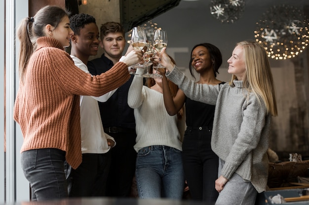 Group of positive young people toasting with wine