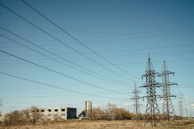 Group of posts with wires of high voltage on background of blue sky. background image of pillars and wires in sky with copy space