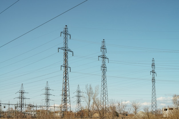 Group of posts with wires of high voltage on scene of blue sky.