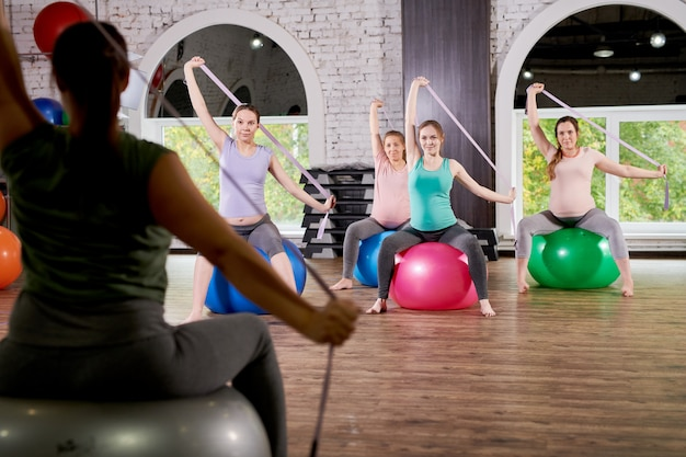 Group of pregnant women stretching in fitness class