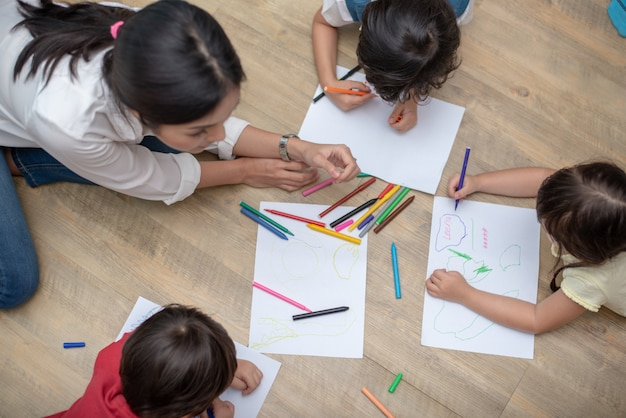 Group of preschool student and teacher drawing on paper in art class.