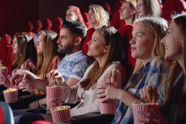 Group of pretty and young female watching new entertaining comedy in cinema hall. cheerful young blonde laughing, eating popcorn and enjoying free time on weekend. concept of happiness and fun.