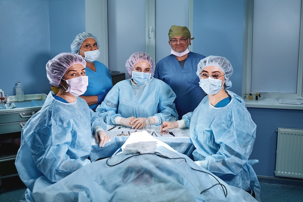 Group of professional doctors surgeons over the clinic in operation room