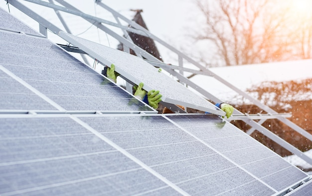 Group of professionals installing photovoltaic solar panels on the roof of modern house during snowy winter time. alternative energy source renewable electricity sun ecological production power plant