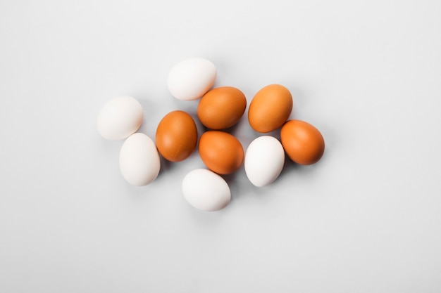 Group of raw eggs white and brown.
