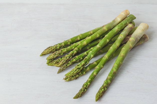 Group of raw green asparagus on white