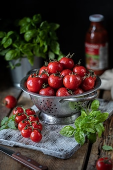 Group of red cherry tomatoes in a metal colander on a wooden table.