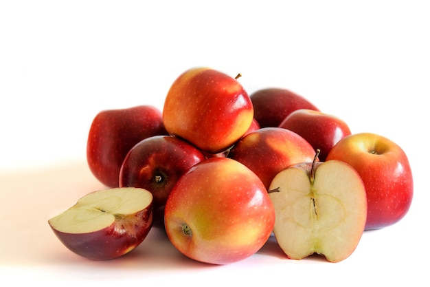 Group of red fresh apples, whole and cut, on the white background.