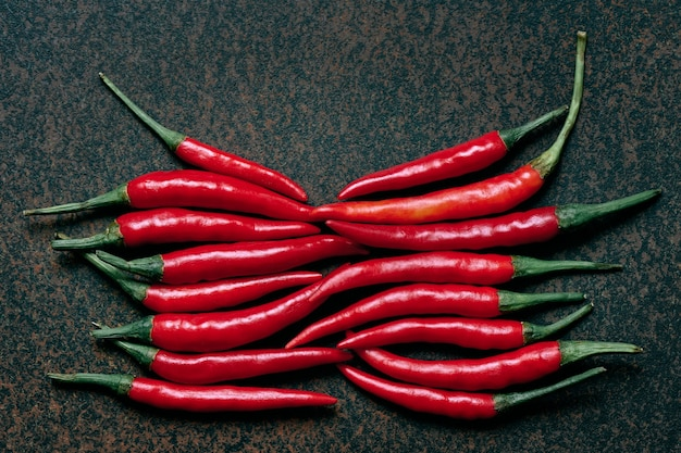 Group of red hot chilli peppers on a dark background, top view