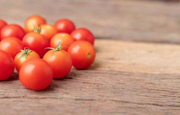 Group red tomatoes on the wooden table