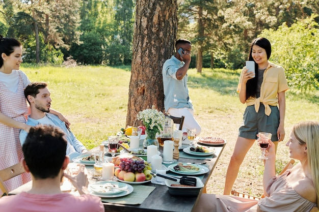 Group of restful friends relaxing by served table after outdoor dinner under pine tree while asian girl taking photo of them in smartphone