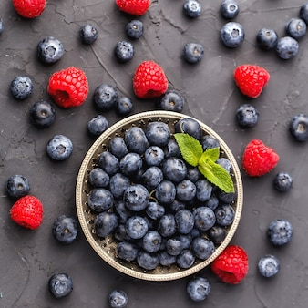 Group of ripe blueberries on metal plate with mint leaves and raspberries