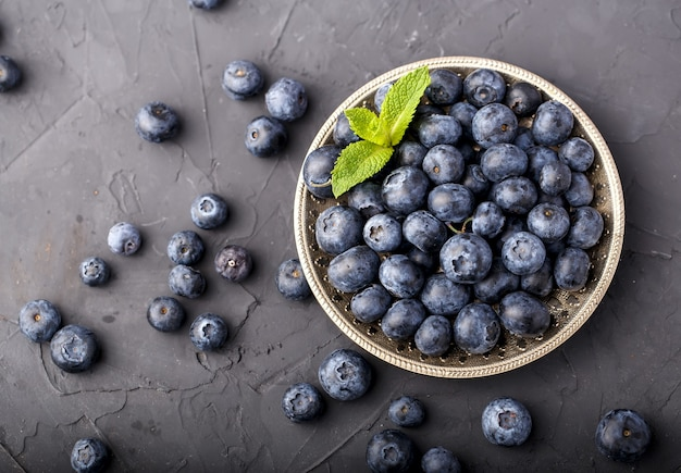 Group of ripe blueberries on metal plate with mint leaves