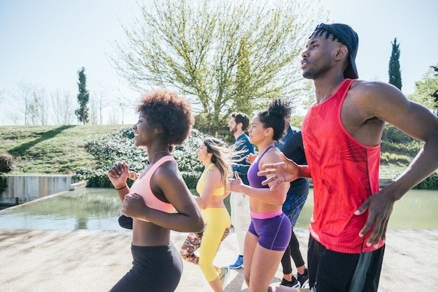 Group of runners training in a park. side view.