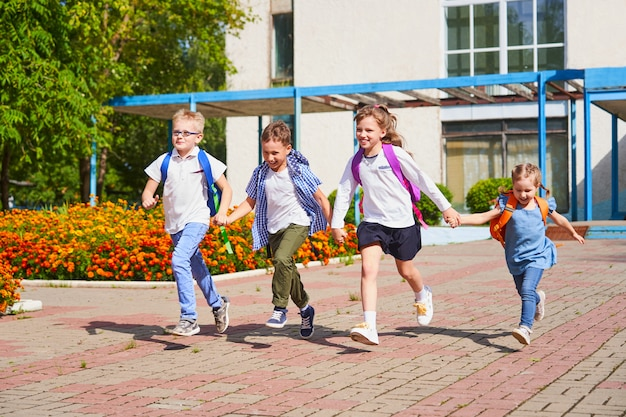 A group of school children running out of school
