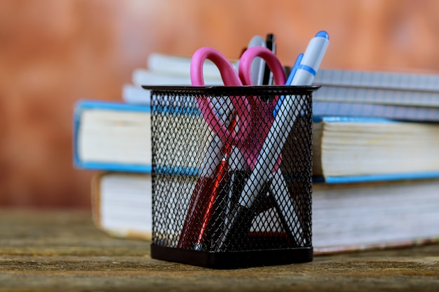 Group of school supplies and books over wood background