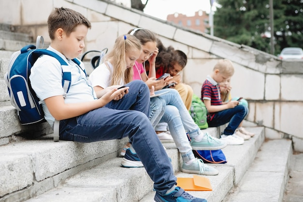 Group of schoolchildren in colorful clothes are sitting on the steps and looking at gadgets. seven classmates of different nationalities.
