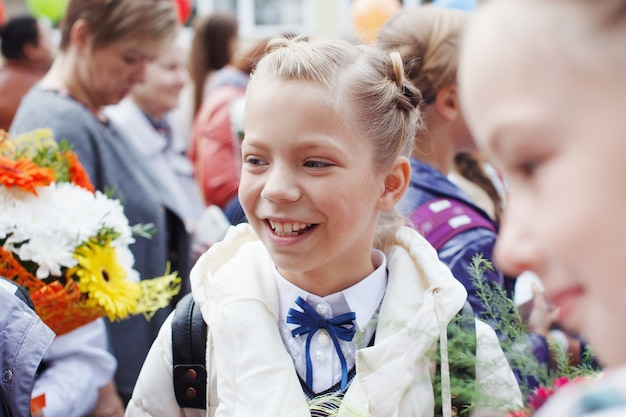 A group of schoolgirls with bows, with flowers go on holiday for education, smile and rejoice.
