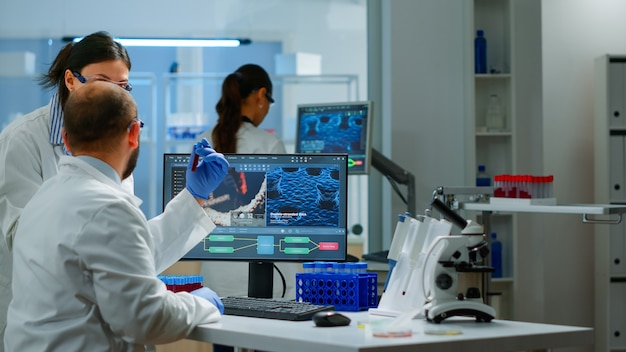 Group of scientists working in modern equipped laboratory pointing on computer desktop. team of doctors examining vaccine evolution using high tech researching diagnosis against covid19 virus