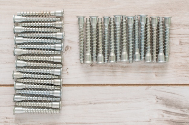 Group of screw bolts for furniture assembling on wooden background. flat lay top view with a copyspace for text. stock photo