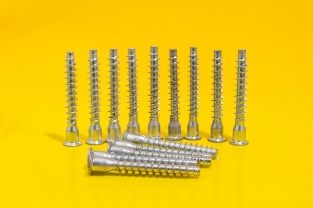 Group of screw bolts for furniture assembling on yellow background. stock photo.