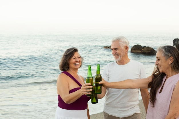 Group of senior friends cheering with beer at the beach