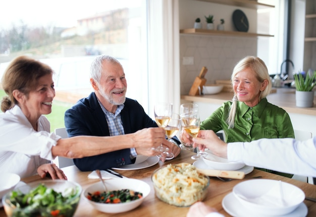 Group of senior friends enjoying dinner party at home, clinking glasses.