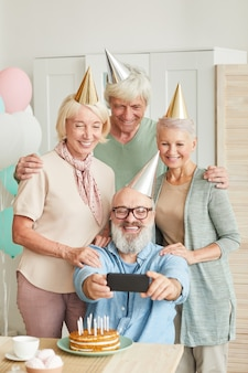 Group of senior friends in hats smiling at camera while making selfie on mobile phone during birthday party