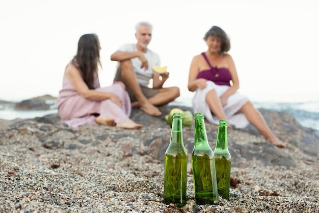 Group of senior friends having beers on the beach
