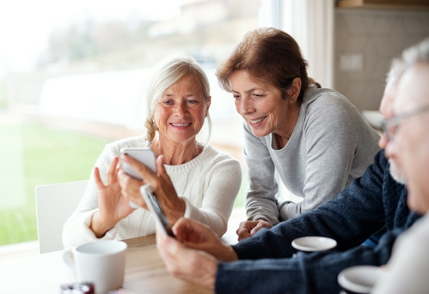 A group of senior friends at home, using smartphones.