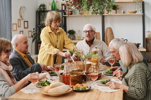 Group of senior people sitting at dining table having dinner and talking to each other at home