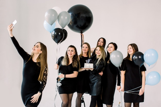 Group of seven girls best friends making selfie on smartphone, enjoying birthday party with cake and air balloons, having fun, smiling and laughing. friendship and birthday party concept