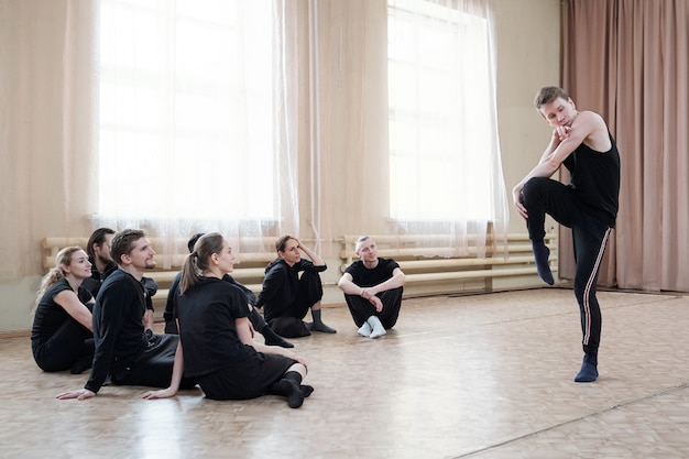 Group of several young dance course students sitting on the floor while looking at guy in activewear doing exercise
