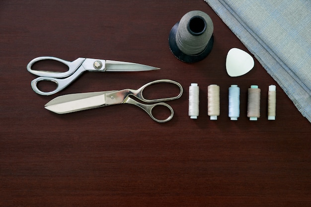 Group of sewing objects lying on a wooden table, flat lay concept of tailor shop