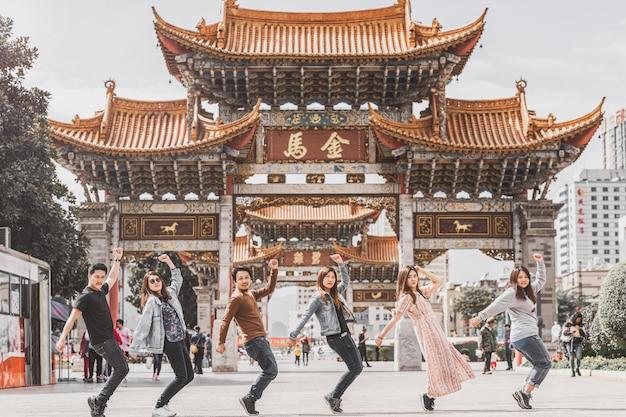 中国昆明の昆明金美広場でのアジアの友情のグループショットアクション、友人船での旅行と観光、ダンスとパロディカバーのコンセプト、中国語のテキストはゴールデンホースとジェイドルースター