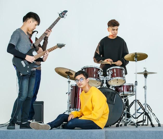 一緒に音楽を演奏する10代のミュージシャンのグループショット。友人が楽器を演奏しながら座ってカメラを見ている黄色のカジュアルな服を着た少年。青年期の関係の概念
